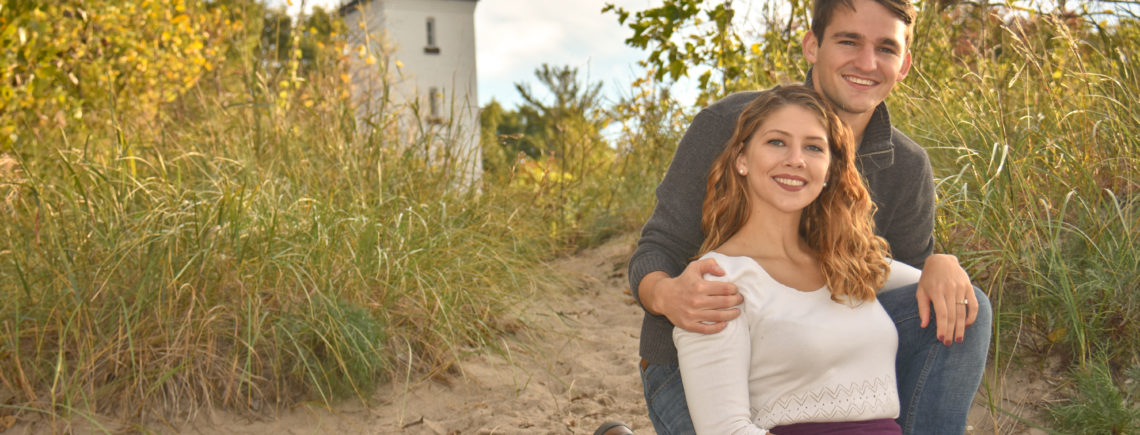 engaged couple at beach in front of light house